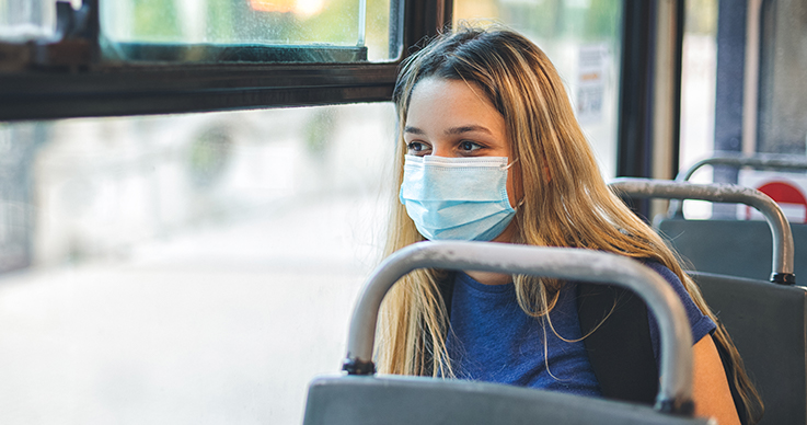 Female student with face mask on public transporation
